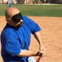 a blindfolded batter takes a swing at the plate.
